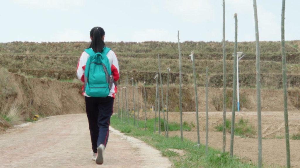 Girl wearing a backpack walking down a dirt road