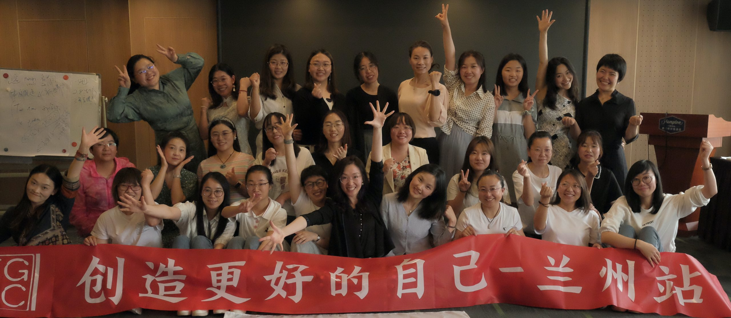 Girls standing behind a red EGRC banner, smiling and waving.